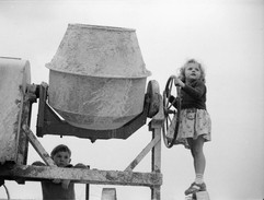 Two children playing with a large cement
