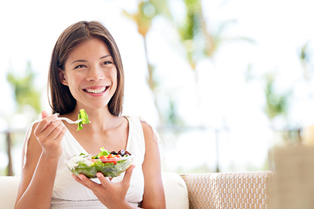 Melhores alimentos para os dias mais quentes moça sorrindo comendo salada