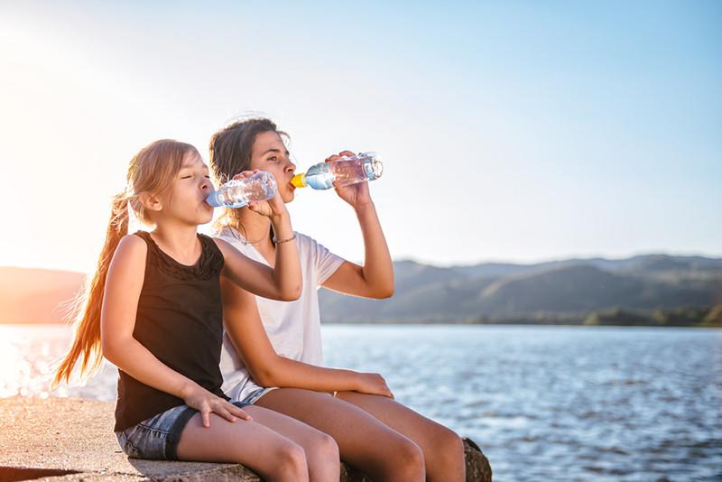importância da hidratação. Crianças bebendo água à beira d'água