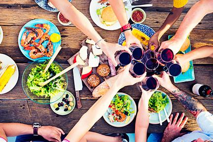 Dicas para manter a boa forma no fim do ano. Grupo de amigos brindando com copo de vinho