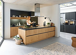 Schuller C Rocca range in natural knotty oaked brushed veneer featuring lava black tall housings and matt black gripledge, peninsular, island extractor