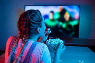 A young girl watching movies and eating
