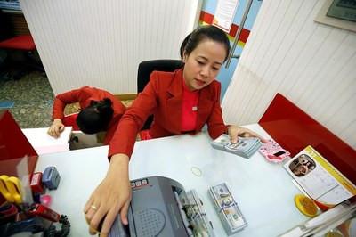 Ảnh minh họa. Nhân viên ngân hàng đếm tiền tại một chi nhánh của HD Bank ở Tp Hồ Chí Minh ngày 12/1/2018.