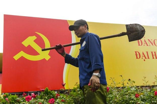 Một công nhân đi ngang qua tấm biển có cờ Đảng Cộng sản ở Hà Nội vào ngày 5 tháng 10 năm 2020.