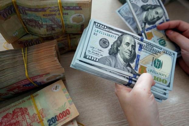 Một nhân viên đếm tiền USD và VND tại chi nhánh ngân hàng VPBank ở Hà Nội ngày 15/11/2017.