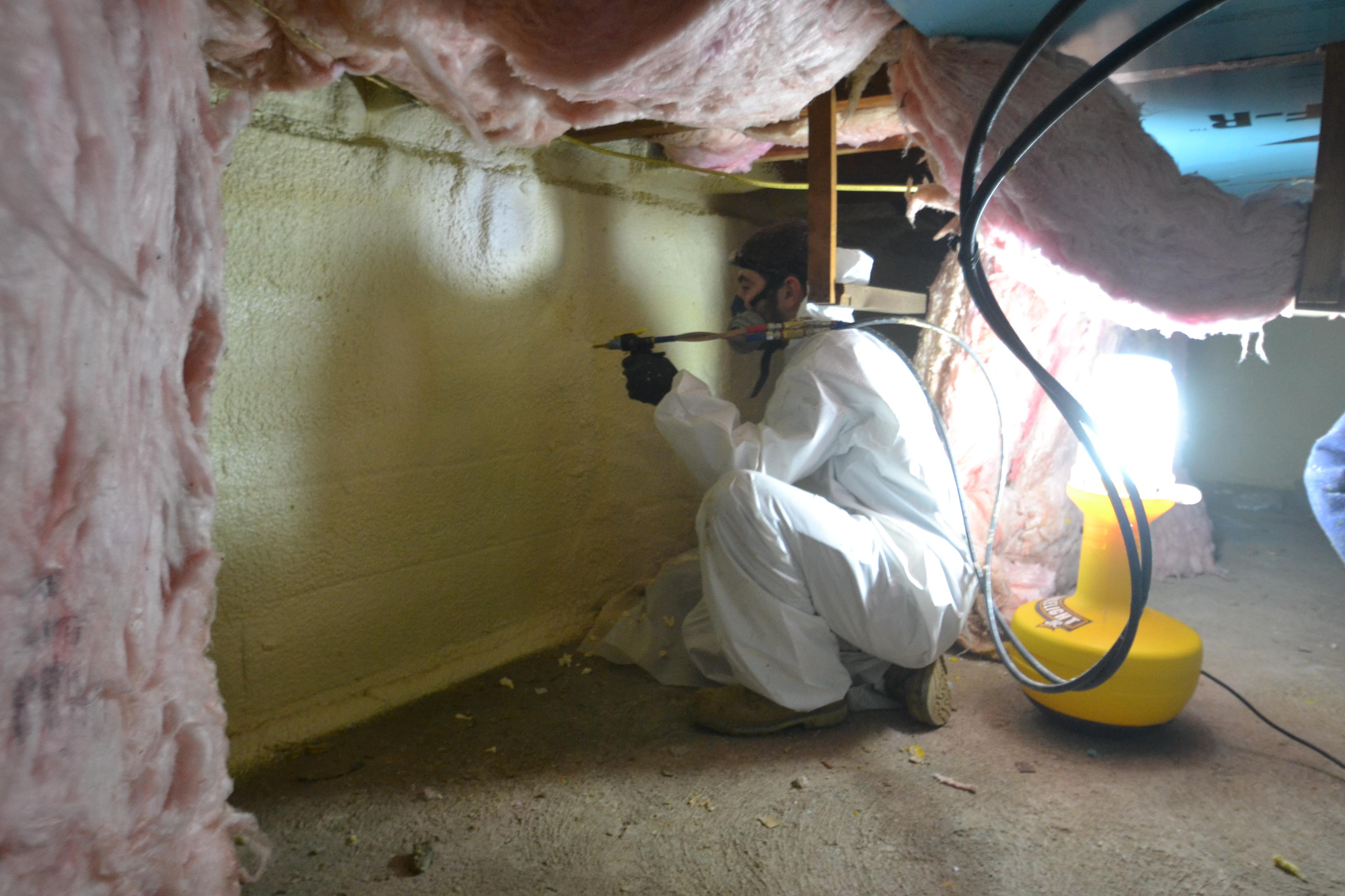 Spray foaming a crawlspace.