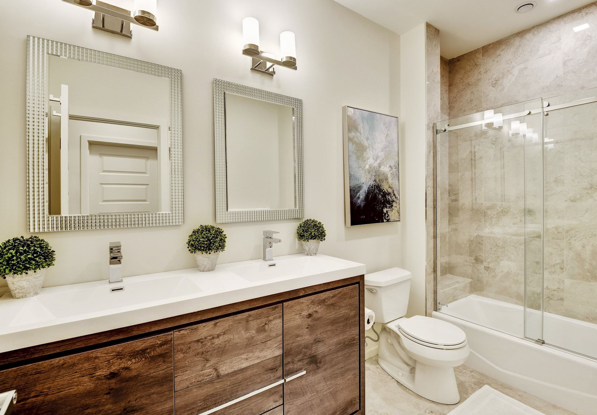 Penthouse bath features dual vanity and frameless tub enclosure