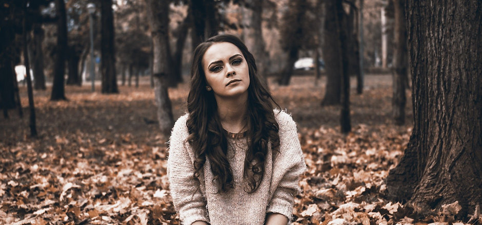 Young Adult Looking Sad on the ground in fallen leaves. Solid Ground Counseling. Teen and adult coun