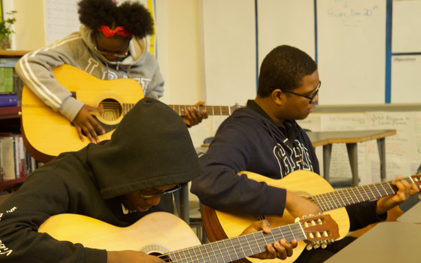 Students practicing to play guitar