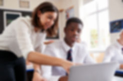 Female Teacher Helping Pupil Using Compu