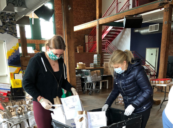Megan and Martha, TAG volunteers, help load the cart with bags of groceries
