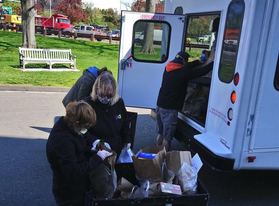 Volunteers load van with groceries