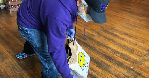 TAG volunteer, Jim, helps take groceries to the TAG van