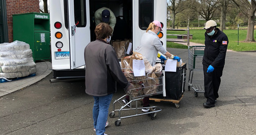 Loading TAG van with bags of groceries.