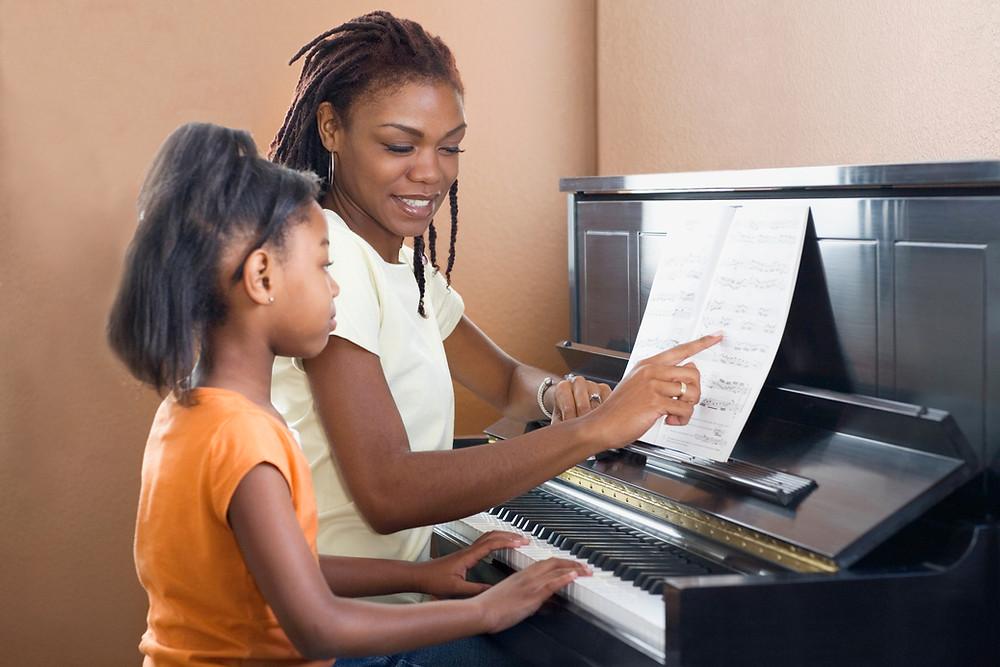 מורה, תלמידה מנגנות מתוך דף תווים