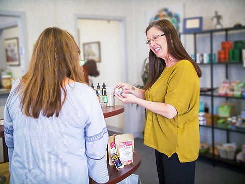 A happy woman in a yellow shirt is showing a customer the CBD products that are for sale inside the store Premier Hemp Company