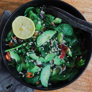 Grönkålssallad med kikärtor, soltorkade tomater och avokadotoppat med pinjenötter