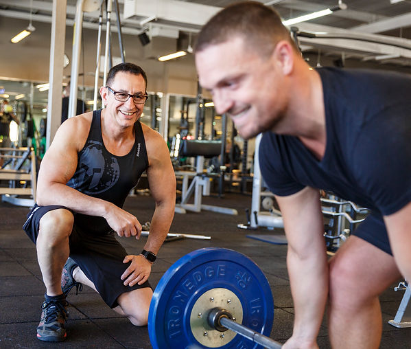 Michael Karimalis Smiling and training a client to lift weights in a gym