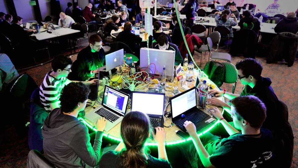 sala llena de computadoras y jóvenes trabajando en ellas