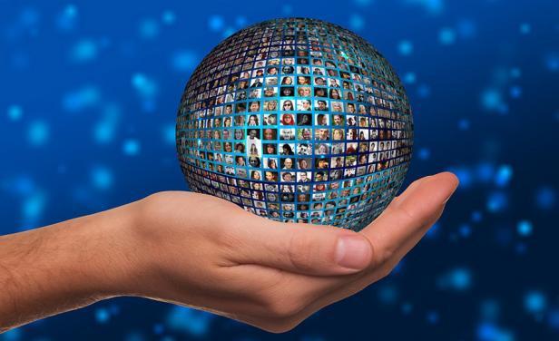 mano que sostiene una esfera llena de imágenes de personas