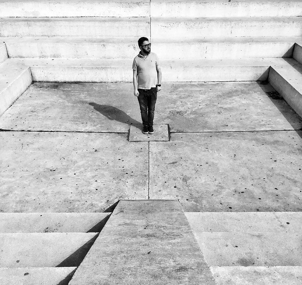 Man standing in the middle of the Bauhouse-inspired sculpture in Edith Wolfson Park.