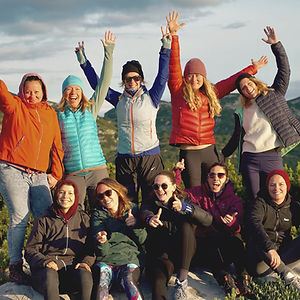 Group of women with arms in the arm celebrating the outdoor community