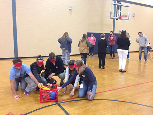 4 people blindfolded kneeling and reaching for objects in a bin in a school gym while other people are standing away from them, facing one another, somewith their backs towards them and others facing them