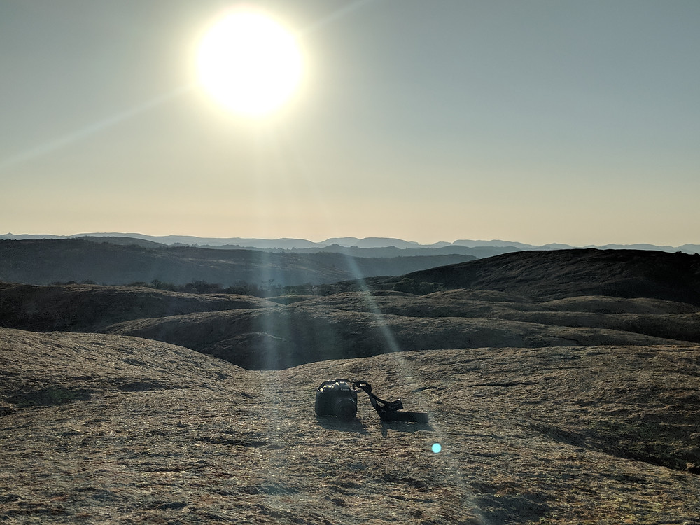 Sunrise at the top of a mountain with a camera placed in view on the mountain