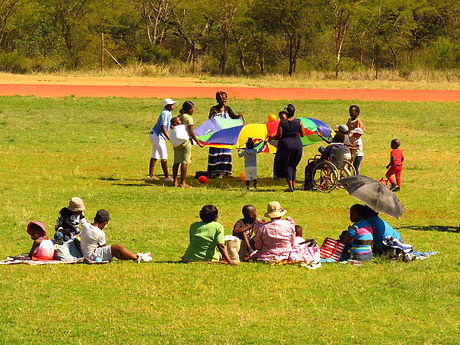 individuals of all ages and abilities playing with a kids' parachute on the field while others watch