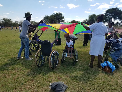 adults helping students using wheelchairs and walkers play with a colorful parachute in a field. One child in a wheelchair is being pushed across underneath the parachute smiling