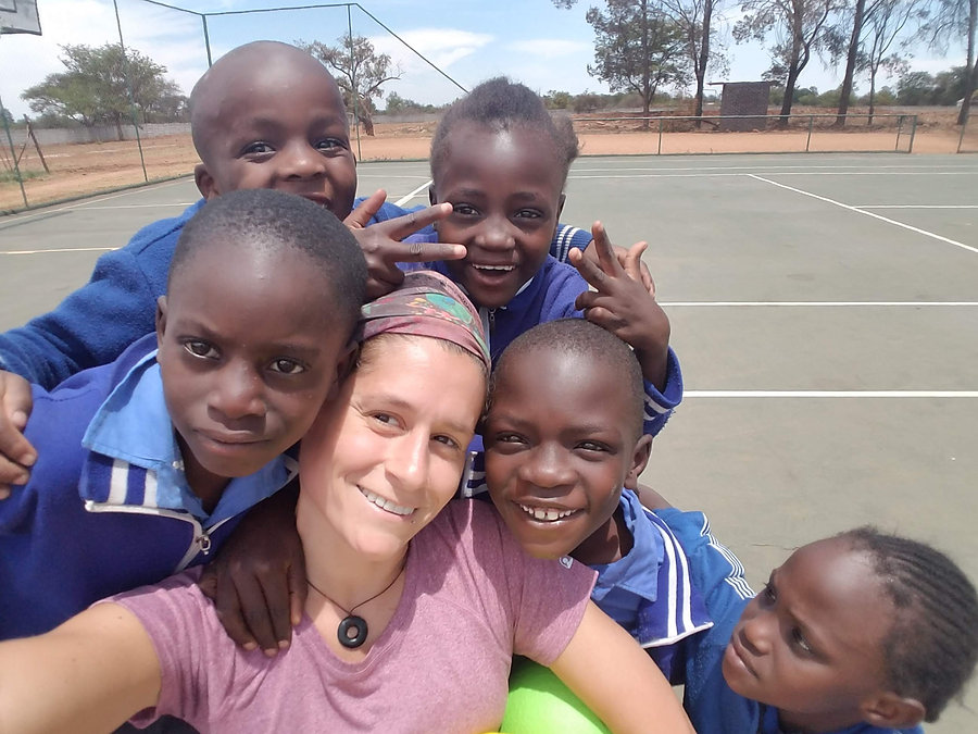 children surrounding and hugging founder, Jess Amato on an outdoor court in Zimbabwe