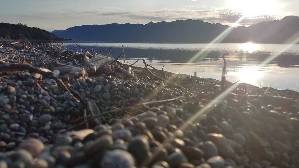 rocky shoreline with a sunset glare.