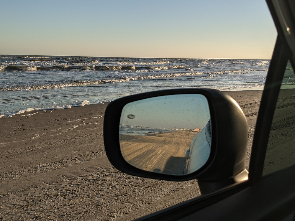 view looking out the driver side of a window while parked on the sand at the beach with the side view mirror showing the view behind the car. Waves crashing and sand