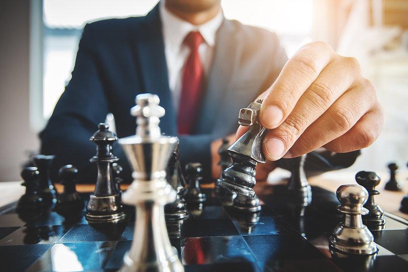 businessman sitting behind chess figure
