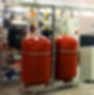 Установка расширительного бака в системе отопления позволяет обеспечить ее работоспособность и надежность. Устройства данного типа используются в открытых и закрытых системах, с самотечной или принудительной циркуляцией теплоносителя.Вода отличается низкими показателями сжимаемости, поэтому в систему встраивают специальное устройство – мембранный или открытый бак. Его функция заключается в том, что при повышении давления сжиматься будет воздух. Это дает возможность обеспечить защиту от гидроудара. Установленный расширительный бак предохраняет систему от чрезмерного повышения давления.Для системы отопления закрытого типа предназначены мембранные баки – они представляют собой емкость с эластичной водонепроницаемой мембраной внутри, которая разделяет внутренний объем на две части. Мембрана нужна, чтобы воздух не контактировал с теплоносителем. В противном случае не избежать завоздушивании сети и повышения риска коррозии стальных элементов системы.  В системе открытого типа бак сообщается