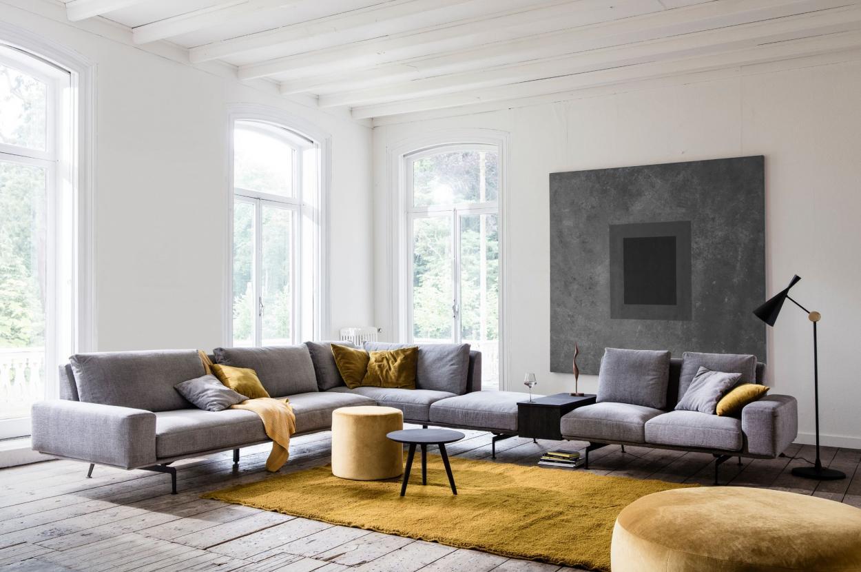 Grijze sofa met okergele sierkussens