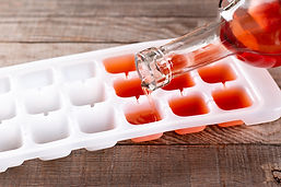 Pouring wine in ice cube tray on a wooden table.jpg