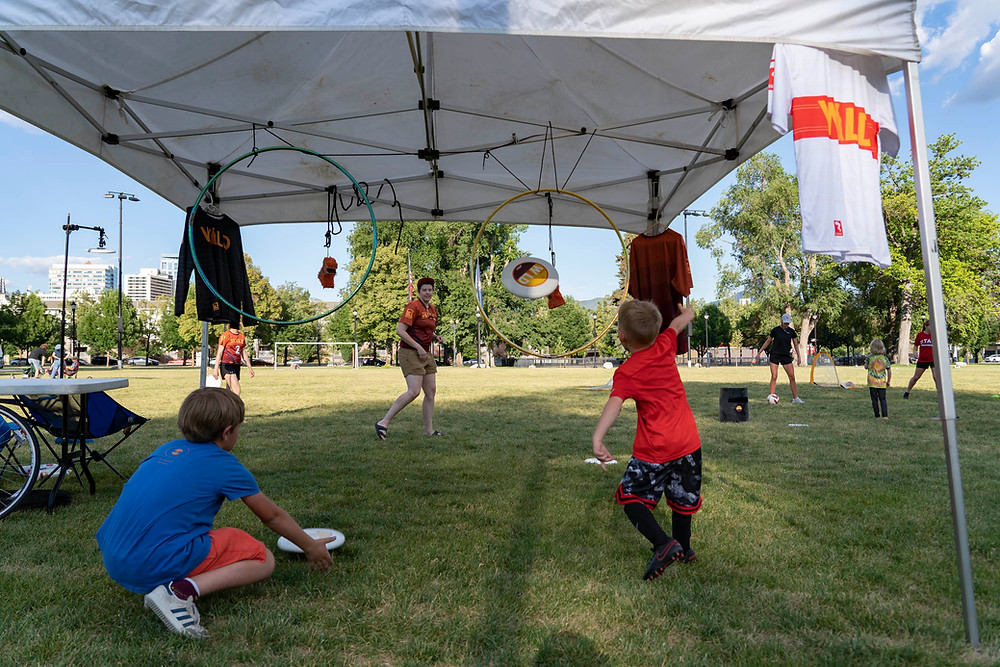 Two young children face away from the camera and throw Utah Wild branded frisbees through hanging hula hoops. Wild jerseys hang on the side and a white woman with a Wild jersey on prepared to catch the disc in the background.