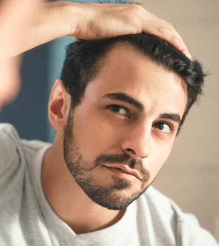 Man looking in the mirror at his hairlin