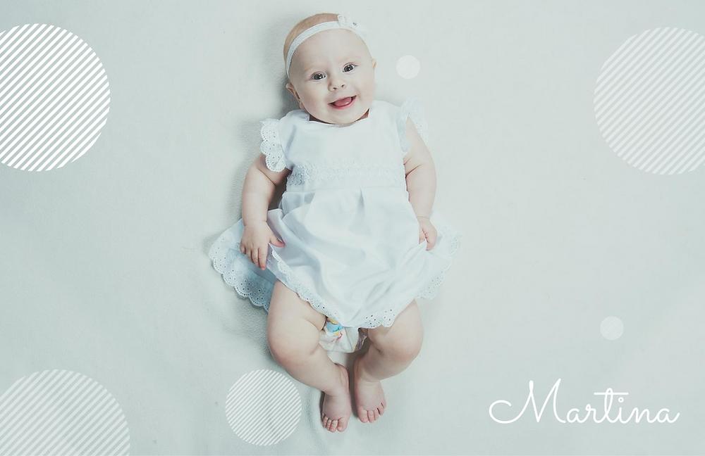 Bebé sonriente con vestido y diadema blanca