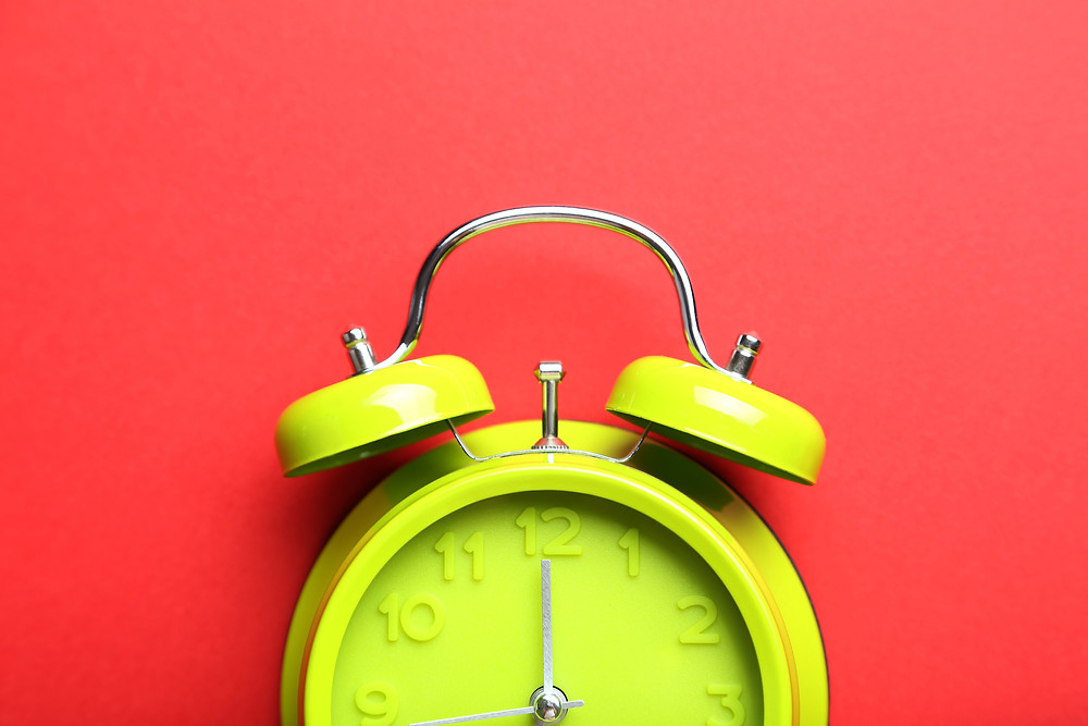 A yellow-green alarm clock on a white backdrop