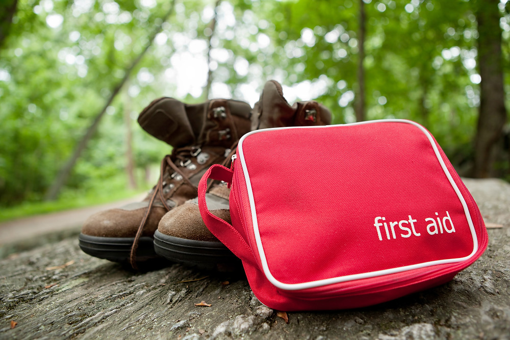 first aid kit next to a pair of hiking boots