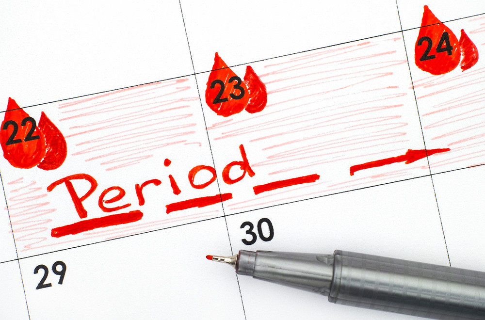 Someone writing down what day they are getting their period.