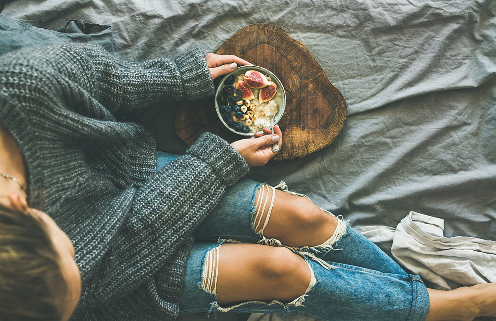 Girl in sweater and jeans sitting on her bed with something healthy