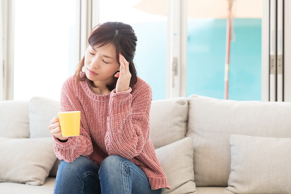 woman in pink sweater holding a mug and has a headache