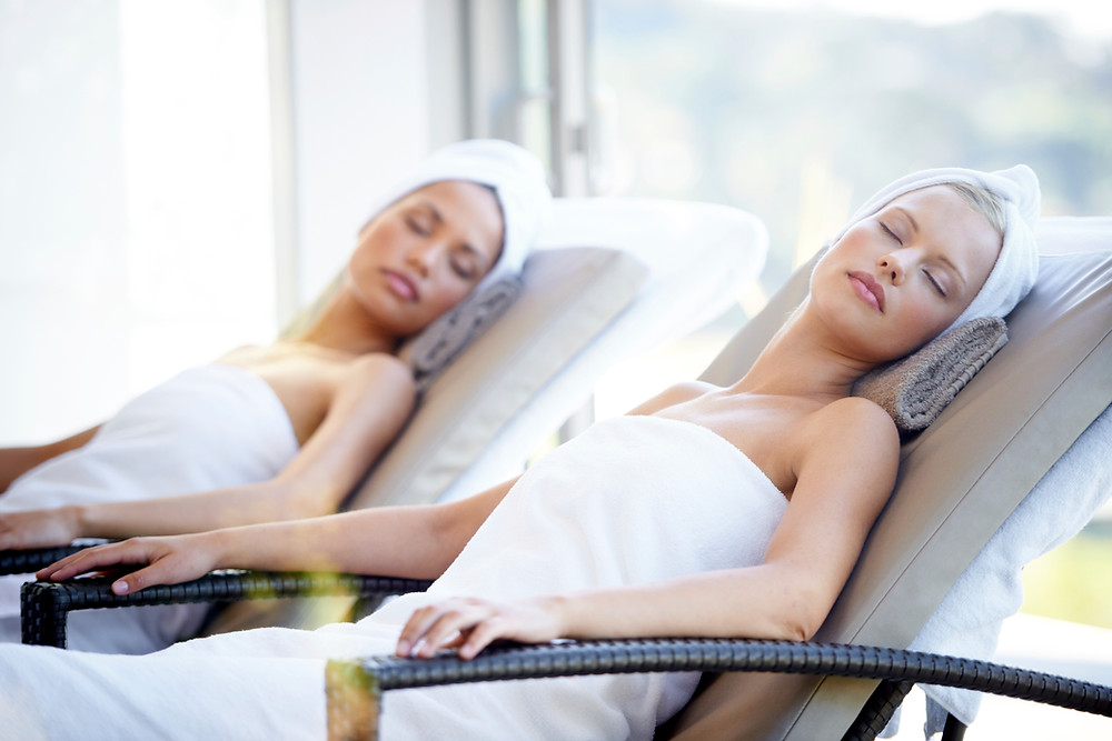 Two women in towels resting on lounge chairs at a spa.