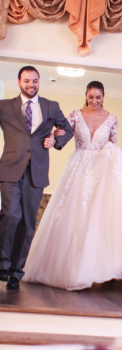 bride and groom walking into the ballroo