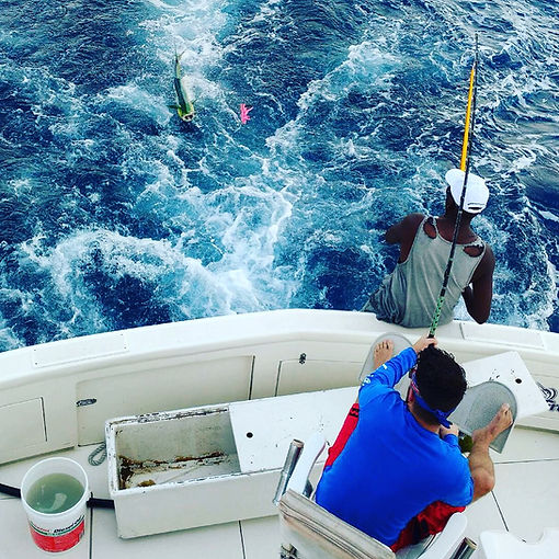 Man fighting a mahi off the stern of a boat
