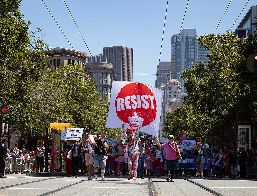 "Front of 2019 San Francisco Pride Parade with a large poster which says ""Resist"""