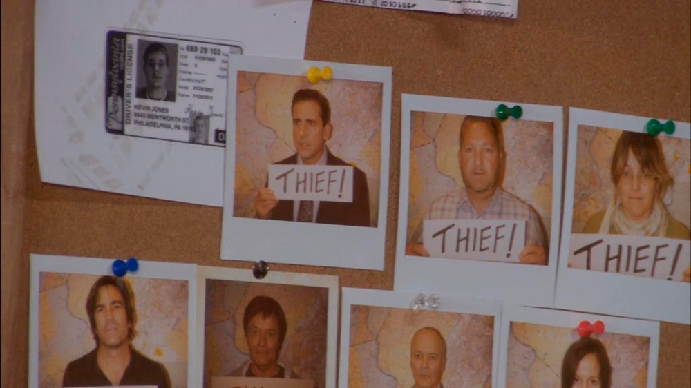 "A bulletin board with Polaroid photographs of people holding a sing that reads ""thief"""